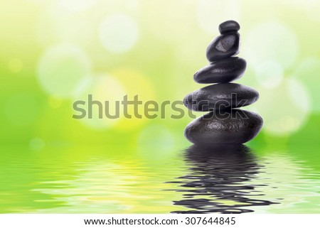 Pyramid of the stones isolated on green bokeh background. Spa Concept. - stock photo