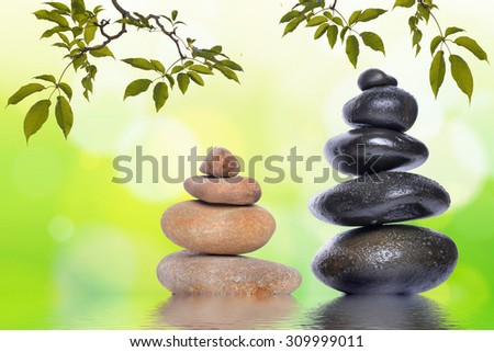 Pyramid of the stones isolated with green leaf on green bokeh background. Spa Concept. Abstract spring green background with leaves and reflection on water - stock photo