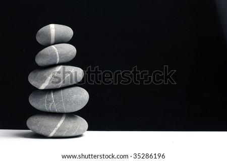 Pyramid of three stones on black - stock photo