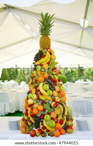 pyramid with tropical fruit on the wedding banquet - stock photo