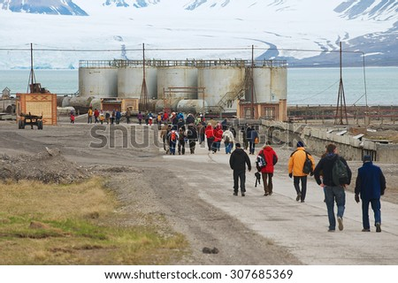 PYRAMIDEN, NORWAY - SEPTEMBER 03, 2011: Unidentified tourists visit abandoned Russian arctic settlement Pyramiden, Norway. - stock photo
