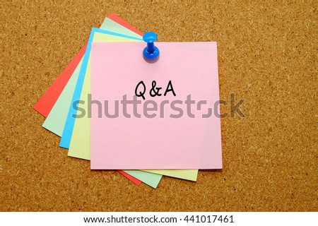 Q&A written on color sticker notes over cork board background.