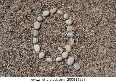 Q letter made of stones on sand - stock photo
