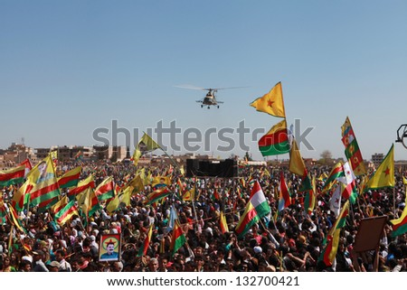 QAMISLO - MARCH 21: More than 20,000 Kurds celebrated Kurdish Festival Newroz. The Syrian Army military helicopter flyed over the meeting on 21 March 2013 in Qamlo, Syria. - stock photo