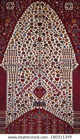 Qashqai tribal village handmade Persian wool rug from Southern Iran, with mihrab arch and tree of life design - detail. - stock photo
