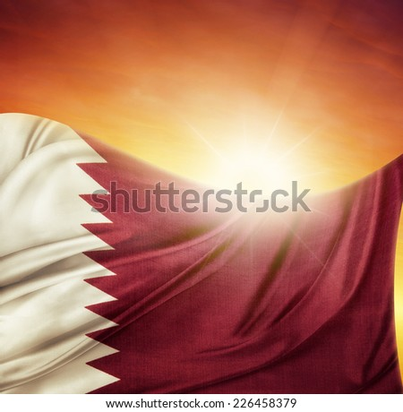 Qatar flag in front of bright sky - stock photo