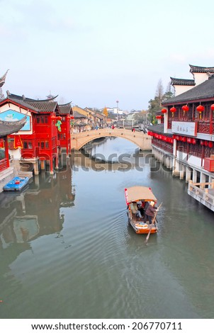 QIBAO, SHANGHAI-DECEMBER 4, 2007: village canal and old bridge at sunset. Qibao water village is Shanghai tourist attraction with 1000000 visitors year. - stock photo