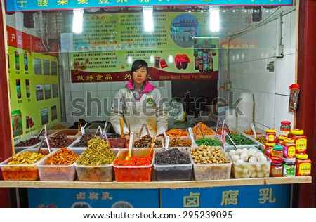 QIBAO, SHANGHAI-MARCH 16, 2010: vendor proposing typical Chinese snacks. Qibao water village is Shanghai tourist attraction with 1000000 visitors year. - stock photo