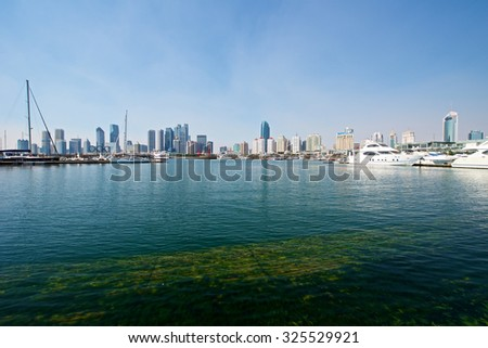 Qingdao, China - September 17, 2015: A beautiful view of Qingdao Skyline harbor with sailboats. - stock photo