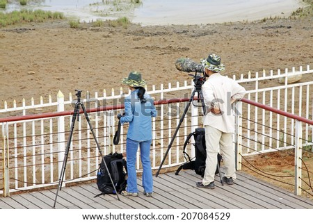 QINHUANGDAO CITY- JUNE 1: A man and a woman two photographers were photographing in a wetland park, June 1, 2014, Qinghuangdao city, Hebei Province, China