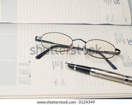 qlasses, calendars and the pen - stock photo
