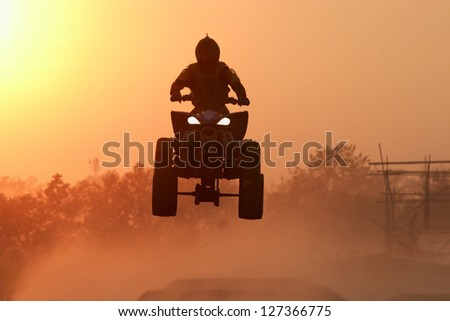 Quad bike Jump in the sunset - stock photo