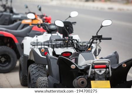 quad bikes alone the road are prepared for hiring - stock photo