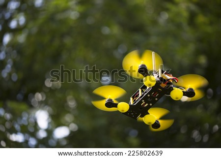 Quadcopter in air with out of focus background. - stock photo