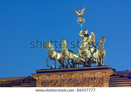 Quadriga on the Brandenburg Gate (Brandenburger Tor) in Berlin, Germany at night. The sculpture made from copper depicts Victoria, the roman goddess of victory, with a chariot (quadriga). - stock photo