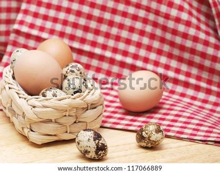 Quail and hen eggs in the kitchen with a towel - stock photo