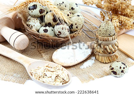 Quail eggs, flour and cooking utensils on canvas isolated on white background. - stock photo