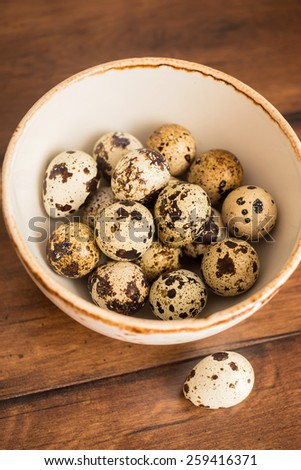Quail eggs in a bowl on the wooden vintage table, selective focus - stock photo