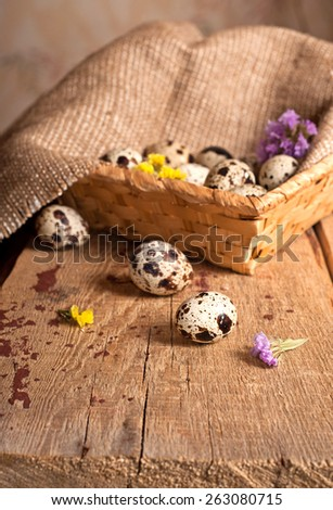 Quail eggs in basket and dry flowers on table - stock photo