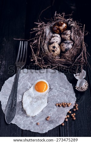 Quail eggs in the nest and a fried egg on a wooden board - stock photo