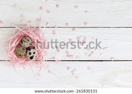Quail eggs in the nest on the wooden table. Top view with copy-space. - stock photo
