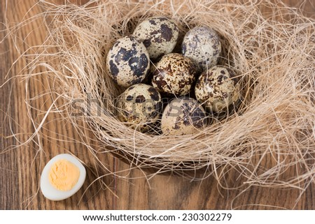 quail eggs lying in a wooden bowl on the table - stock photo