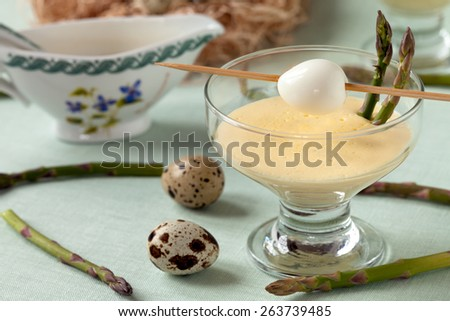 Quail eggs served with wild asparagus and mustard mayonnaise. - stock photo