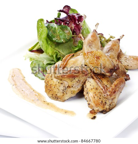 Quail with green salad on white plate - stock photo