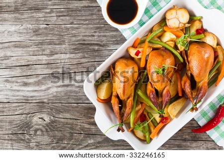 quails baked with vegetables - potatoes, green beans, chilli pepper, garlic and carrots, decorated with basil leaves, in the baking dish, on the old table, top view - stock photo