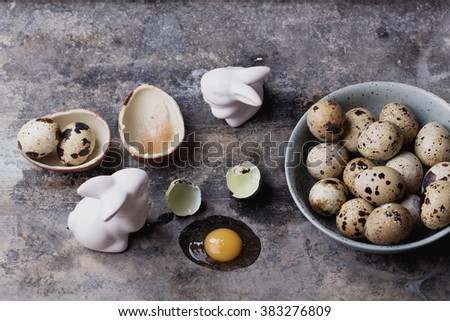 Quails Eggs  and white ceramic bunny with flowers and chocolate egg in an old spotted bowl against a rustic background with selective focus. A different type of concept image for Easter. - stock photo