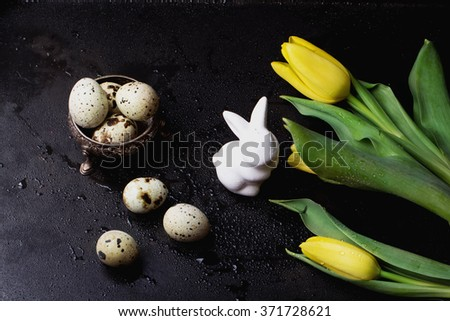 Quails Eggs  and white ceramic bunny with yellow tulip flowers on an old spotted bowl against a rustic background with selective focus. A different type of concept image for Easter.