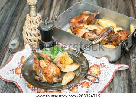 Quails fried in the owen with potatoes - stock photo