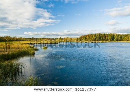 Quaint autumnal landscape with small lake - stock photo