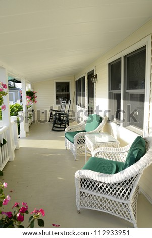 quaint covered porch with white wicker chairs and black rocking chairs - stock photo