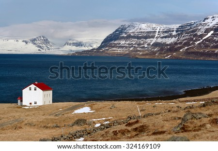 Quaint isolated farm house along the fjord westfjords surrounded by mountains covered in snow in Iceland - stock photo