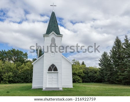 quaint little country church sitting in a green meadow surrounded by trees in the summer time - stock photo