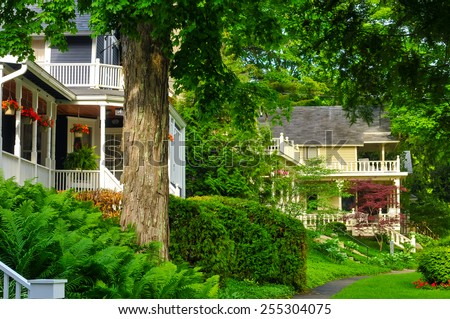 Quaint old homes line a tree-shaded street in an older neighborhood - stock photo