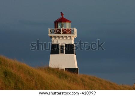 quaint summer-side lighthouse watching the coast of Prince Edward Island - stock photo