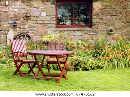 Quaint Table and Chairs in Vibrant Garden of Rustic Country Cottage - stock photo