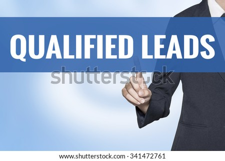 Qualified Leads word on virtual screen touch by business woman blue background - stock photo