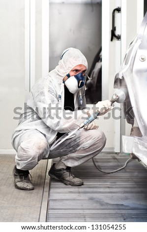 qualified worker spraying grey paint on a car in special painting booth - stock photo