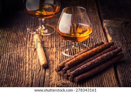 quality cigars and cognac on an old wooden table