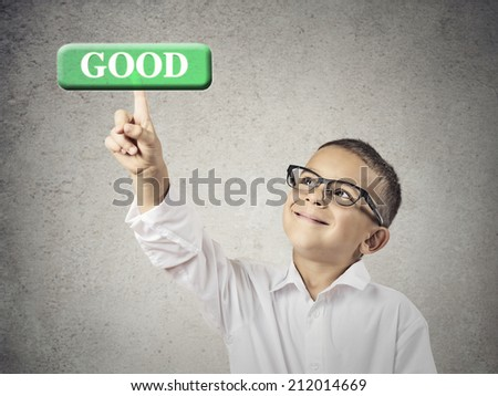 Quality control. Boy hand press good button. Happy, smiling child with glasses clicks green icon on touch screen display, isolated grey wall background. Positive face expression, emotions, perception - stock photo
