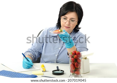 Quality control expert carefully examines at the half strawberry in the laboratory