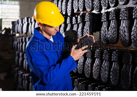 quality controller checking rubber-boots sole in storeroom - stock photo