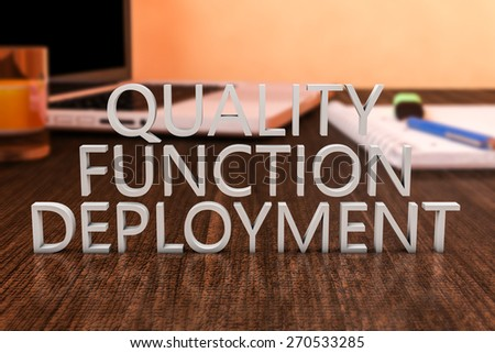 Quality Function Deployment - letters on wooden desk with laptop computer and a notebook. 3d render illustration. - stock photo