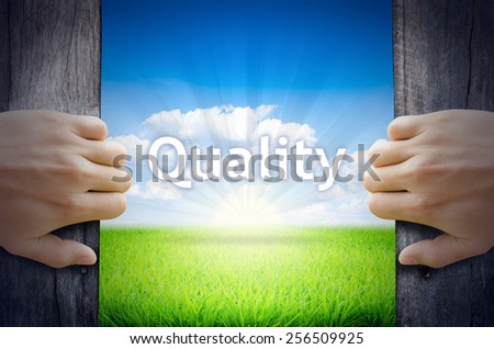 Quality . Hand opening an old wooden door and found Quality word floating over green field and bright blue Sky Sunrise. - stock photo