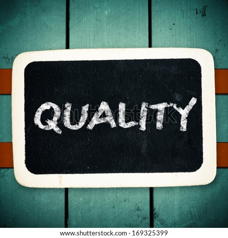 Quality handwritten with white chalk on a blackboard on wood background  - stock photo