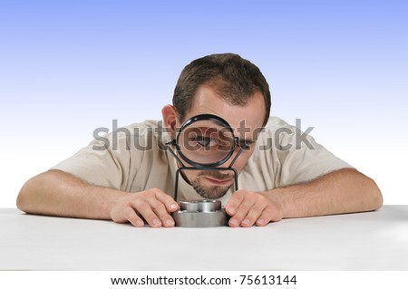Quality Inspector looking through  a magnifying glass checking a product - stock photo