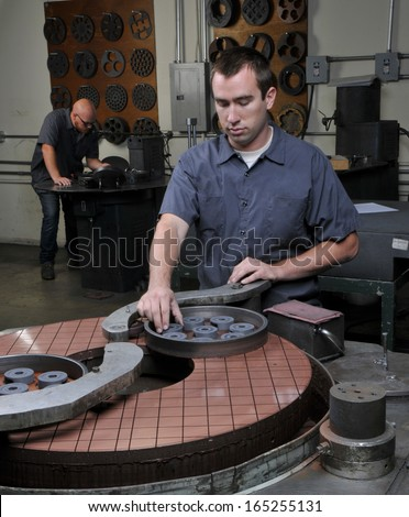 Quality Inspector/Worker in a Precision Machine Shop checking manufactured parts - stock photo